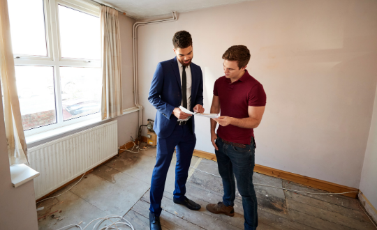 Buyer and surveyor looking over property survey